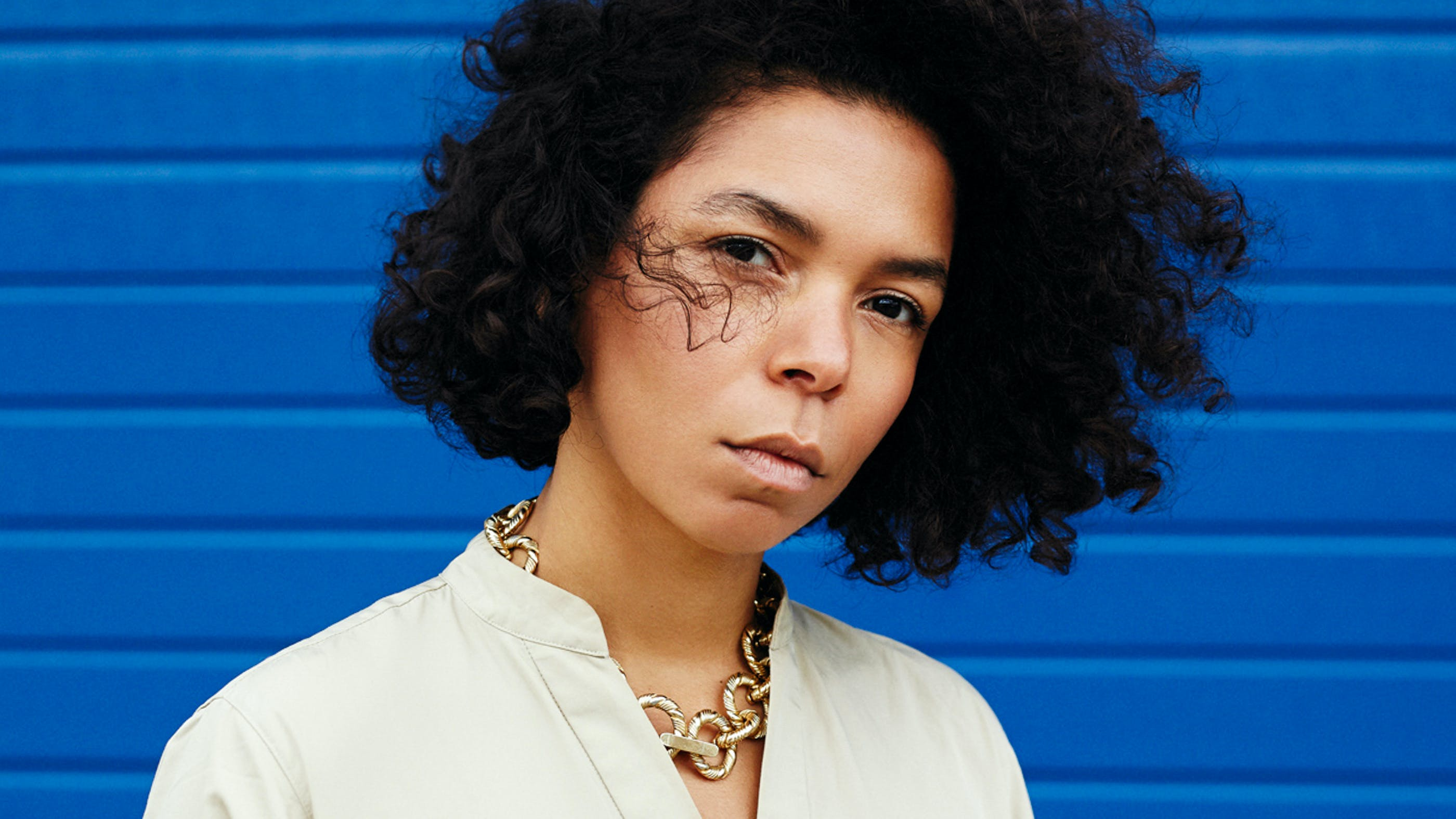 Wir sehen die Autorin Katharina Warda, wie sie heute aussieht. Locken, braune Augen und einen relativ ersten Gesichtsausdruck, fotografiert vor einer blauen Wand.