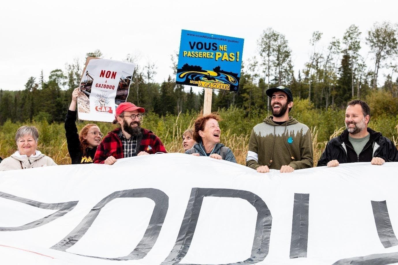 Mitglieder verschiedener Umweltschutz-Bündnisse singen an der Grenze zwischen Ontario und Québec Slogans gegen das Erdgasprojekt.