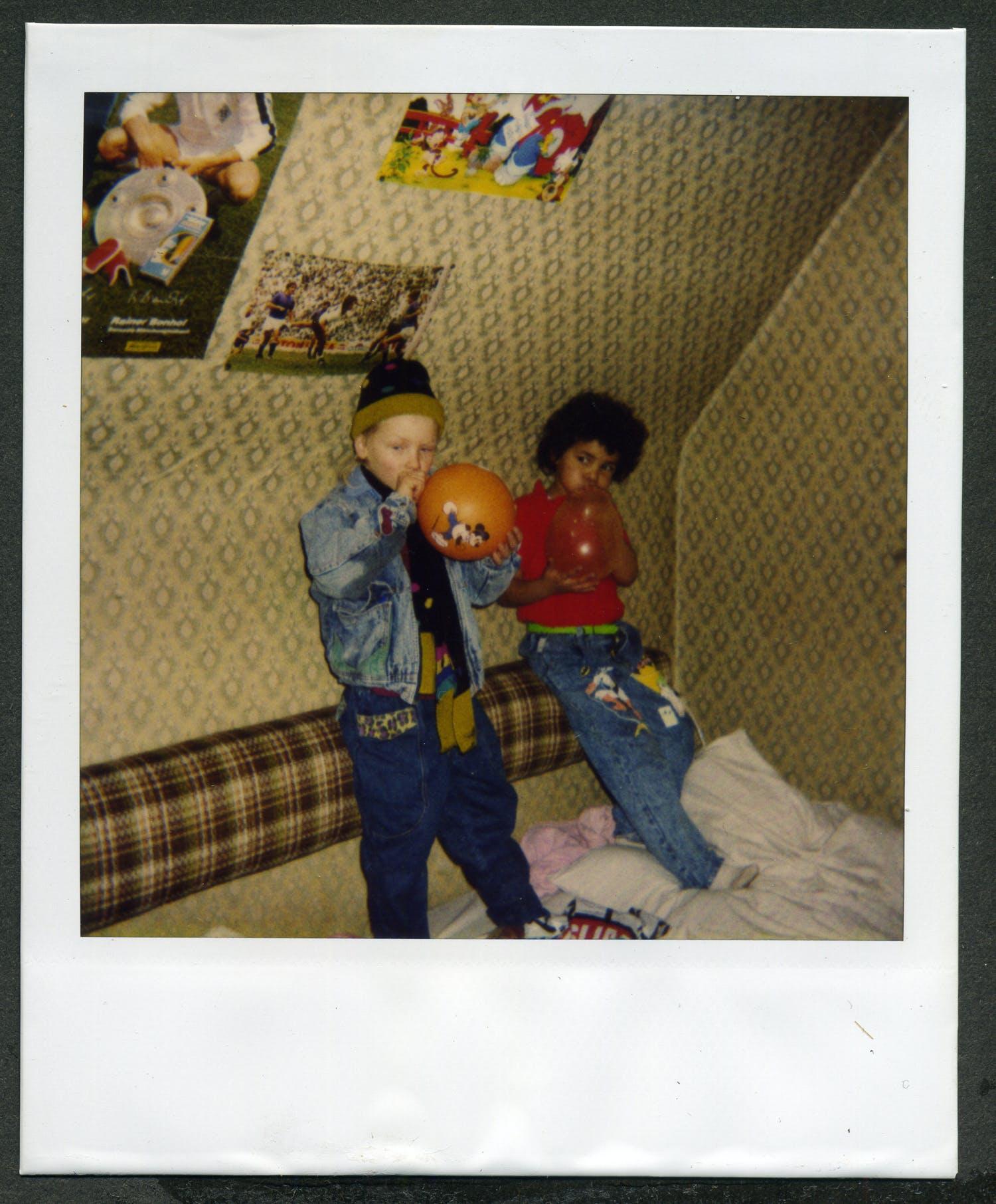 Wir sehen die Autorin in vermutlich ihrem Kinderzimmer im Alter von sieben Jahren. Neben ihr steht ein weißer Junge gleichen Alters und bläst einen orangenen Luftballon auf.